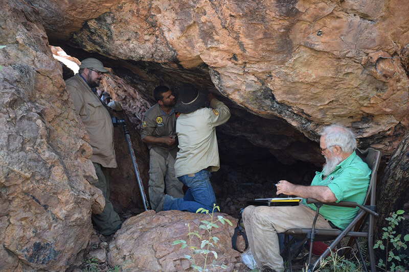 Project archaeologist and rangers looking at rock art