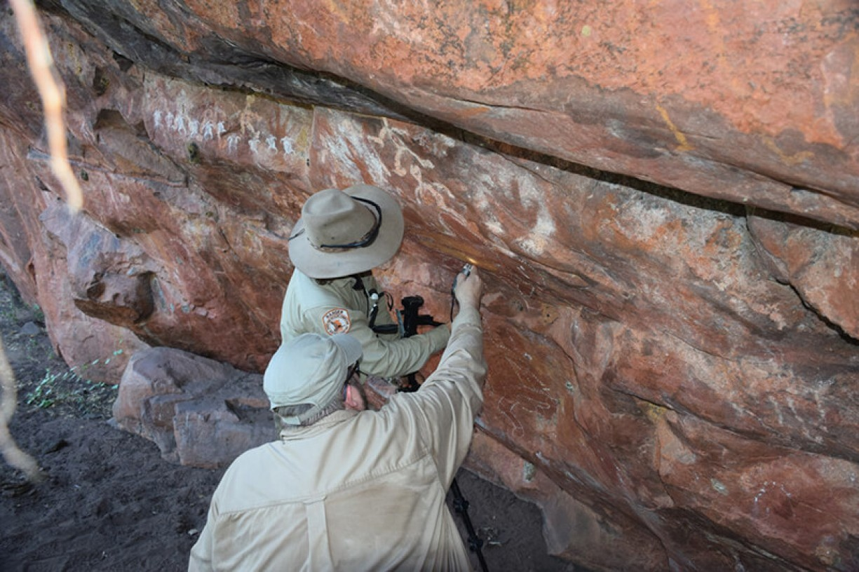 Rangers setting up the camera to access the state of the rock art pigment